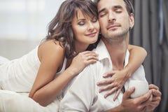 Acople o homem e a mulher em casa na cama com uma xícara de café Fotografia de Stock