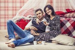 Acople o homem e a mulher no quarto em casa que bebem o chá com bi foto de stock