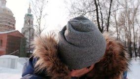 Acople o homem e a mulher que falam na conexão video, beijos e andando no parque da cidade do inverno no dia nevado com neve de q video estoque