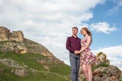 Acople o indivíduo novo com uma menina que guarda as mãos que estão e que olham afastado no fundo de uma paisagem bonita das roch Fotografia de Stock