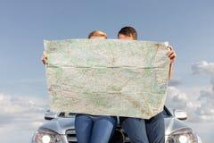 Acople o mapa da leitura ao inclinar-se na capa do carro durante a viagem por estrada fotos de stock royalty free