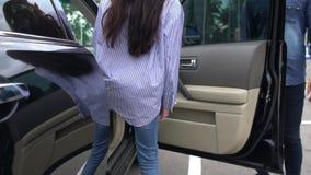 Acople o passeio acima a um carro estacionado em um parque de estacionamento video estoque