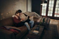 Acople o relaxamento com um portátil na sala de visitas acolhedor fotografia de stock