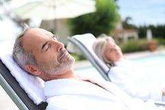 Acople o relaxamento em cadeiras longas no dia ensolarado Fotografia de Stock