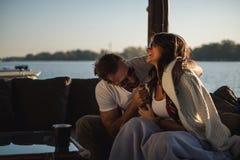 Acople o riso e a apreciação do por do sol ao sentar-se pelo rio imagens de stock royalty free