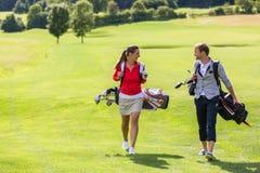 Acople o saco de golfe levando ao andar no campo de golfe imagem de stock royalty free