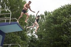 Acople o salto de uma placa de mergulho em uma natação fotos de stock royalty free