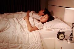Acople o sono em uma cama confortável no quarto na noite fotos de stock