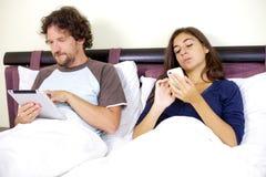 Acople o trabalho na cama com tabuleta e telefone Imagem de Stock Royalty Free