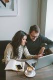 Acople o trabalho no café com portátil, smartphone e café Fotos de Stock