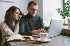 Acople o trabalho no café com portátil, smartphone e café Foto de Stock