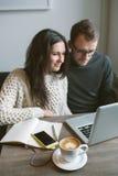 Acople o trabalho no café com portátil, smartphone e café Imagens de Stock