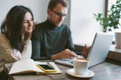 Acople o trabalho no café com portátil, smartphone e café Fotos de Stock Royalty Free