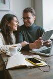Acople o trabalho no café com tabuleta, portátil, smartphone, bloco de notas Imagem de Stock