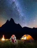 Acople os caminhantes que sentam-se junto perto da fogueira e da barraca de incandescência na noite sob estrelas e que olham ao c Fotos de Stock Royalty Free