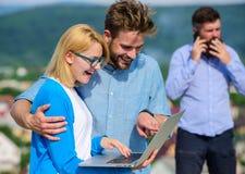 Acople os colegas que flertam quando chefe ocupado com conversação móvel Benefícios móveis do Internet Vídeo do uso dos colegas fotos de stock