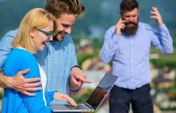 Acople os colegas que flertam quando chefe ocupado com conversação móvel Móbil da videoconferência do uso dos colegas pelo contrá fotos de stock