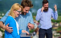 Acople os colegas que flertam quando chefe ocupado com conversação móvel Móbil da videoconferência do uso dos colegas pelo contrá imagens de stock