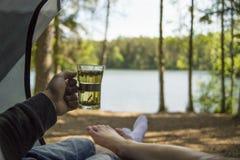 Acople os pés que encontram-se junto na barraca aberta que bebe uma caneca de chá Fotografia de Stock Royalty Free