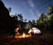 Acople os turistas que descansam ao lado do acampamento, barraca da fogueira na noite foto de stock royalty free