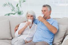 Acople os vidros bebendo do leite que sentam-se no sofá Imagem de Stock