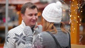 Acople passar o tempo engraçado no mercado do Natal, homem que ri e que fala a uma mulher, família nova feliz alegre video estoque