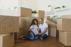 Acople planear sua situação nova da sala de visitas no assoalho família nova que move-se para um apartamento novo e umas caixas l fotografia de stock