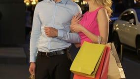 Acople a posição na rua com sacos de compras, menina que falam ao indivíduo e sorriso filme