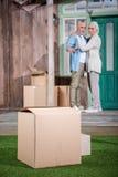 Acople a posição no patamar da casa nova e de olhar caixas de cartão na grama Imagens de Stock Royalty Free