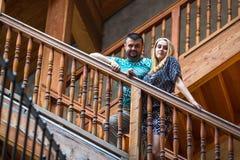 Acople a posição em uma escada de madeira do vintage na casa Foto de Stock Royalty Free