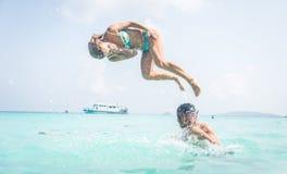 Acople ter o divertimento na água clara bonita Imagens de Stock Royalty Free