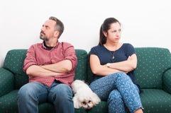 Acople ter uma discussão ao sentar-se no sofá fotografia de stock