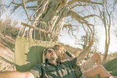 Acople a tomada do selfie na rede que pendura da árvore enorme do Baobab no savana africano Opinião de Fisheye, imagem tonificada Fotos de Stock Royalty Free