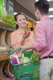 Acople vegetais de compra no supermercado, guardarando a cesta imagem de stock