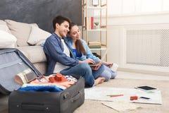Acople a viagem do planeamento, consultando no portátil em casa imagens de stock royalty free