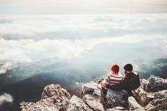 Acople viajantes homem e mulher que sentam-se no penhasco foto de stock