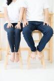 Acople wearings camisa branca e calças de ganga que sentam-se na cadeira de madeira Fotos de Stock
