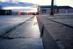 Acordar a uma elevação do sol na calha de alguma cidade pequena com uma chuva ligeira que vem para baixo imagem de stock