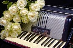 Acordeão do vintage e um ramalhete das rosas brancas Imagem de Stock Royalty Free
