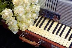 Acordeão do vintage e um ramalhete das rosas brancas Conceito de uma música nostálgica Fotos de Stock Royalty Free