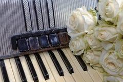 Acordeão do vintage e um ramalhete das rosas brancas Conceito de uma música nostálgica Imagens de Stock
