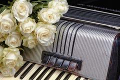 Acordeón del vintage y un ramo de rosas blancas Imagen de archivo libre de regalías
