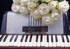 Acordeón del vintage y un ramo de rosas blancas Fotografía de archivo libre de regalías