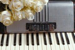 Acordeón del vintage y un ramo de rosas blancas Concepto de no. Imagen de archivo