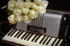 Acordeón del vintage y un ramo de rosas blancas Concepto de una música nostálgica Fotos de archivo libres de regalías