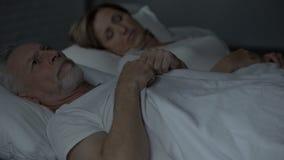 Acorde a cabeça masculina idosa da fricção, olhando a mulher que dorme ao lado, problemas vídeos de arquivo