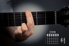 Acorde de la guitarra en un fondo oscuro La C undécimo es un acorde de la seis-nota Digitación de la etiqueta C11 fotos de archivo