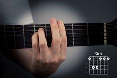 Acorde de la guitarra en un fondo oscuro Acorde de menor importancia de G Digitación de la etiqueta del Gm imagenes de archivo