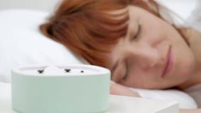 Acorde de uma menina adormecida que para o despertador na cama na manhã filme