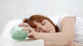 Acorde de uma menina adormecida que para o despertador na cama na manhã vídeos de arquivo